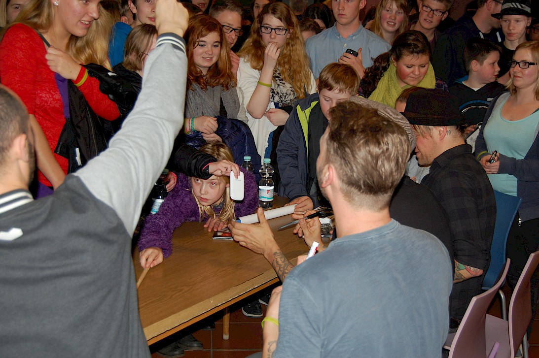 Band members sign autographes for the pupils