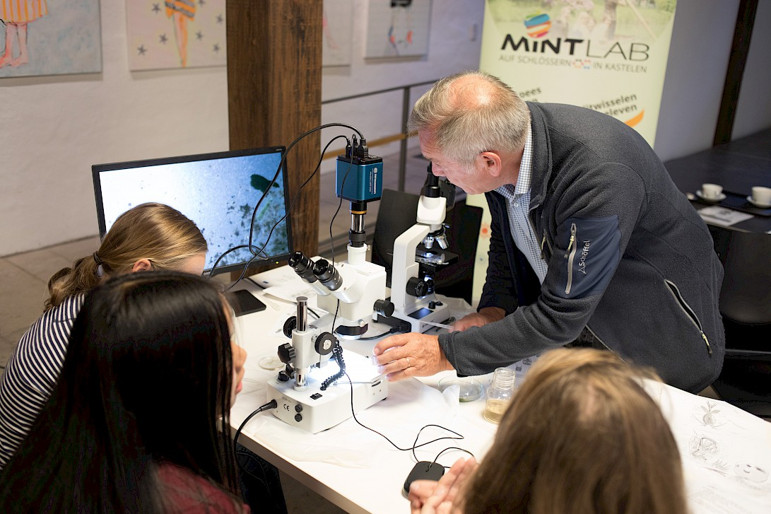 Teacher shows pupil how to operate the microscope