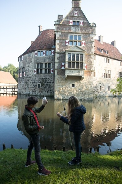 Two students examine their water samples, in the background are the castle grounds.