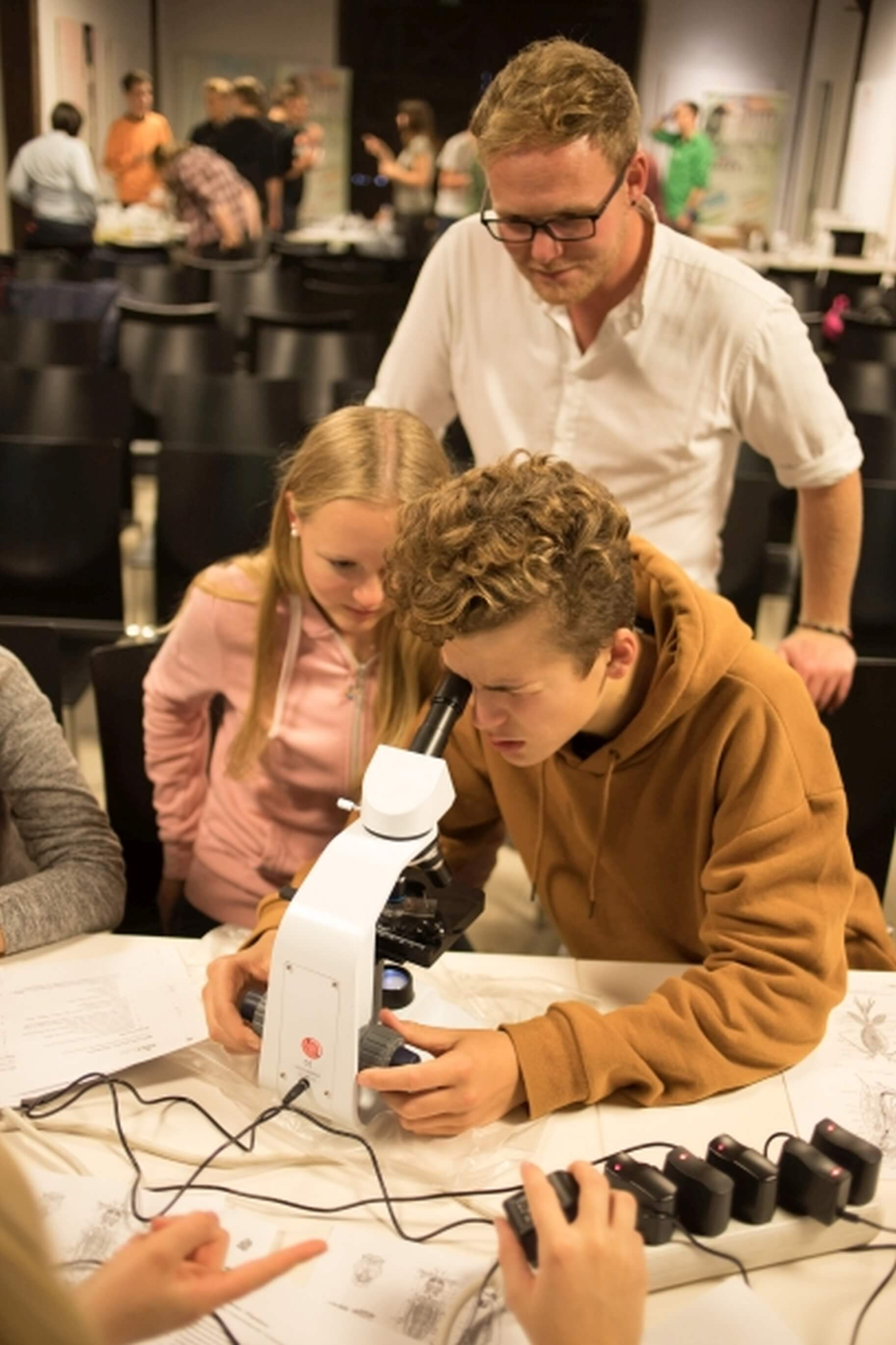 Students look through the microscope, teacher stands behind them
